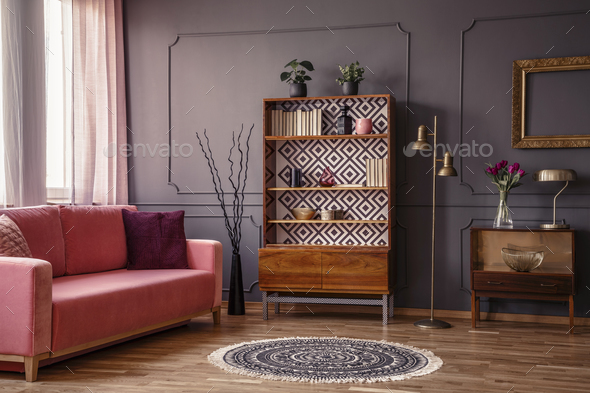 Antique wooden bookcase with decorations in an elegant gray livi - Stock Photo - Images