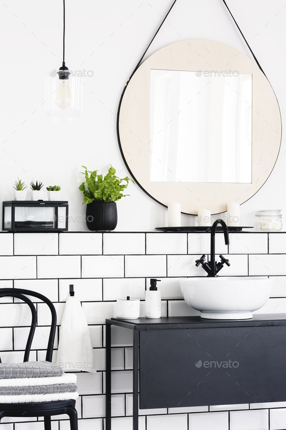 Real photo of a toilet interior with a mirror, plant, chair and - Stock Photo - Images