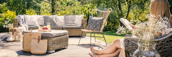 Woman reading a book on patio with rattan table, chair and sofa - Stock Photo - Images