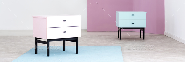 White cabinet on blue rug near cupboard against violet wall in l - Stock Photo - Images