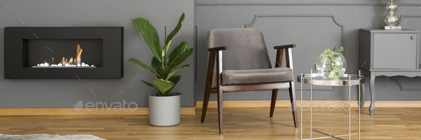 A silver side table and an elegant, upholstered armchair in a mo - Stock Photo - Images
