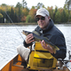 Happy fisherman holds up a walleye on a northern Minnesota lake - PhotoDune Item for Sale
