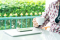 Male hand holding smart phone and cup of coffee_ - PhotoDune Item for Sale