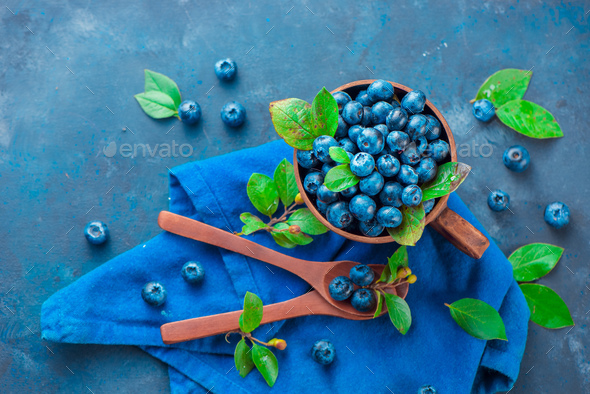 Blueberries in a ceramic cup with wooden spoons and a linen napkin. Ripe and sweet summer berries on - Stock Photo - Images