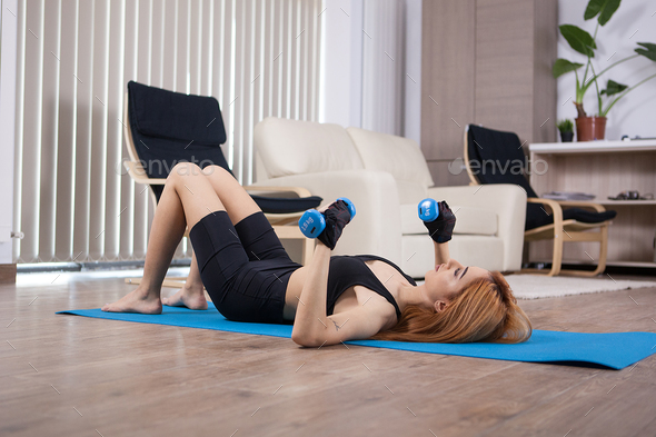 Girl doing home chest workout with dumbbels - Stock Photo - Images