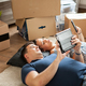 Happy young couple lying on floor near moving boxes. - PhotoDune Item for Sale
