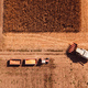 Aerial view of combine harvester pouring corn kernels into cart - PhotoDune Item for Sale