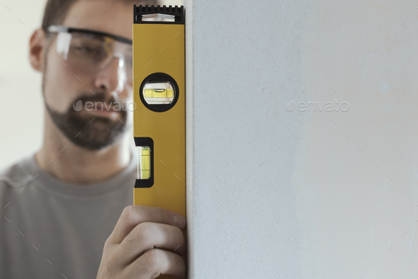Man using a level to plumb a wall - Stock Photo - Images