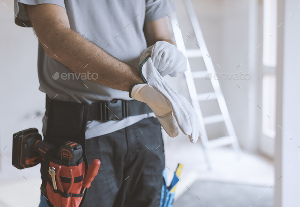 Professional repairman wearing protective gloves - Stock Photo - Images