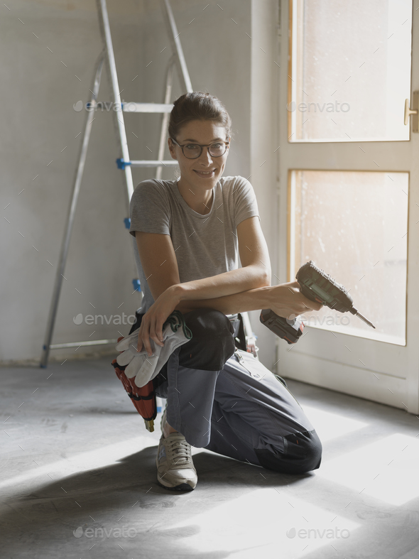 Professional repairwoman posing and holding a drill - Stock Photo - Images