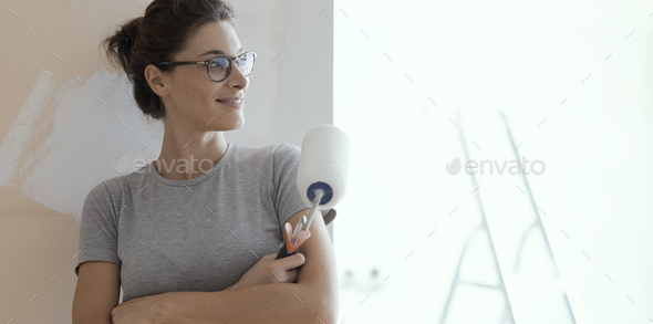 Confident happy woman painting walls at home - Stock Photo - Images