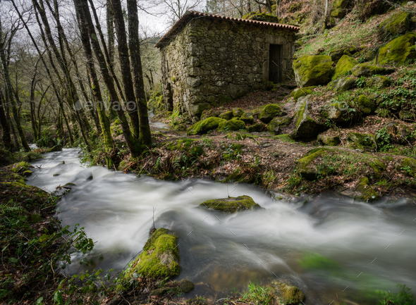 Rural stone house next to a stream - Stock Photo - Images