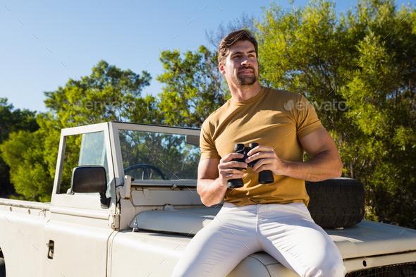 Man holding binocular on off road vehicle - Stock Photo - Images