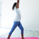 Side view of girl with arms raised exercising in room - PhotoDune Item for Sale
