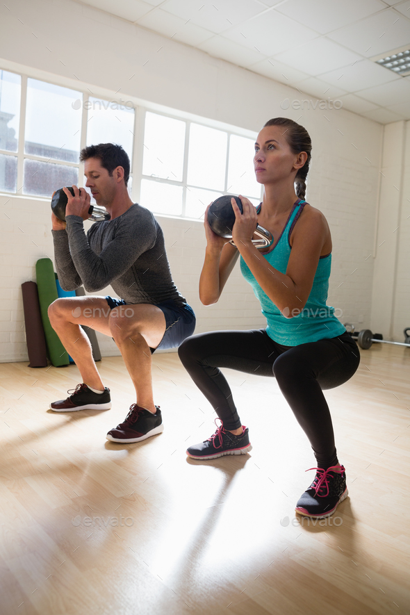 Full length of athletes exercising with kettlebells - Stock Photo - Images