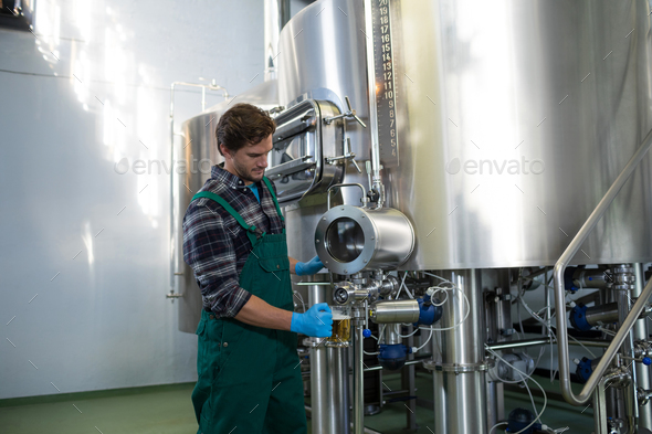 Male worker taking beer from storage tank at factory - Stock Photo - Images
