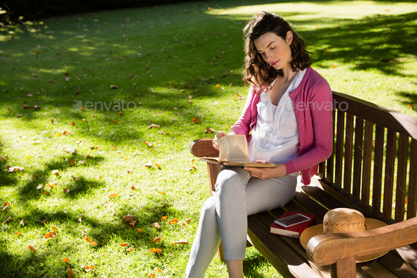 Woman sitting on bench and reading book - Stock Photo - Images