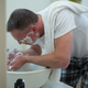 Man spraying water on his face after shaving in the bathroom - PhotoDune Item for Sale