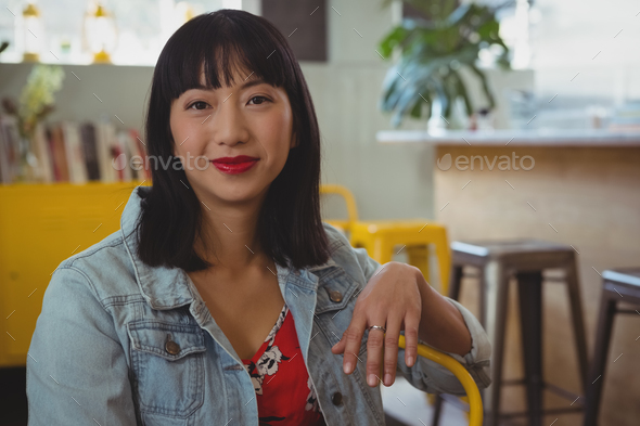Portrait of woman on chair in cafe - Stock Photo - Images
