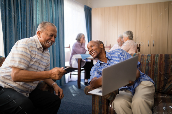 Happy senior man showing laptop to friend - Stock Photo - Images