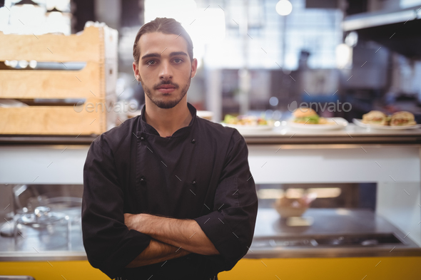 Portrait of confident young waiter standing against counter - Stock Photo - Images