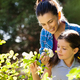 Smiling woman with daughter smelling white roses - PhotoDune Item for Sale