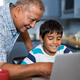 Smiling grandfather assisting grandson using laptop - PhotoDune Item for Sale