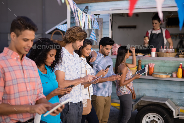 Friends interacting while using mobile phone and digital tablet at counter - Stock Photo - Images