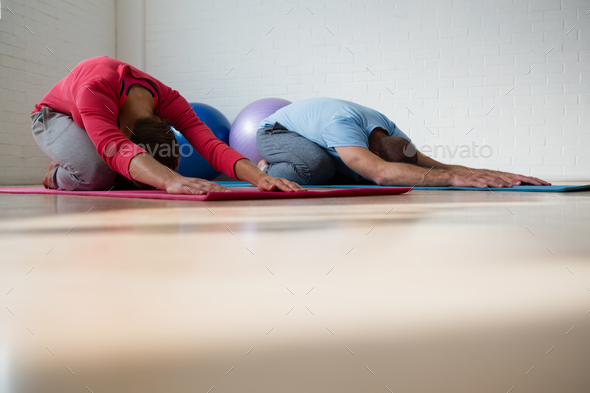 Instructor with student practicing child pose in yoga studio - Stock Photo - Images