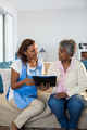 Doctor explaining medication on clipboard to senior woman in living room - PhotoDune Item for Sale