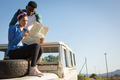 Couple looking at map while sitting on car bonnet - PhotoDune Item for Sale