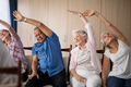 Senior people stretching while sitting on chairs - PhotoDune Item for Sale