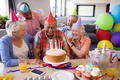 Cheerful friends looking at senior man in birthday party - PhotoDune Item for Sale