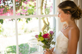 Side view of smiling beautiful bride holding bouquet while looking through window - PhotoDune Item for Sale