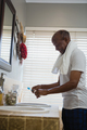 Side view of smiling senior man holding toothpaste and brush in bathroom - PhotoDune Item for Sale