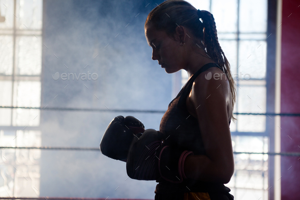 Determined woman standing in boxing ring - Stock Photo - Images