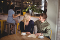 Happy couple talking while sitting with coffee cups and menu at table - PhotoDune Item for Sale