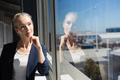 Thoughtful businesswoman looking through window at office - PhotoDune Item for Sale