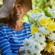 Smiling senior woman wearing hat holding fresh flowers - PhotoDune Item for Sale
