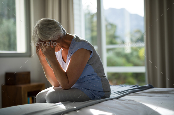 Tense senior woman sitting on bed in bedroom - Stock Photo - Images
