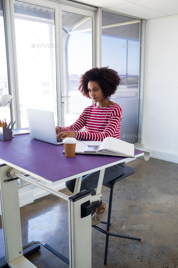 Female executive working over laptop - Stock Photo - Images