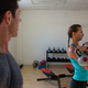 Male trainer looking at female athlete lifting kettlebells - PhotoDune Item for Sale