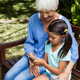 High angle view of smiling grandmother looking at granddaughter using mobile phone on wooden bench - PhotoDune Item for Sale