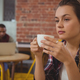 Free Download Thoughtful woman holding coffee cup at cafe Nulled