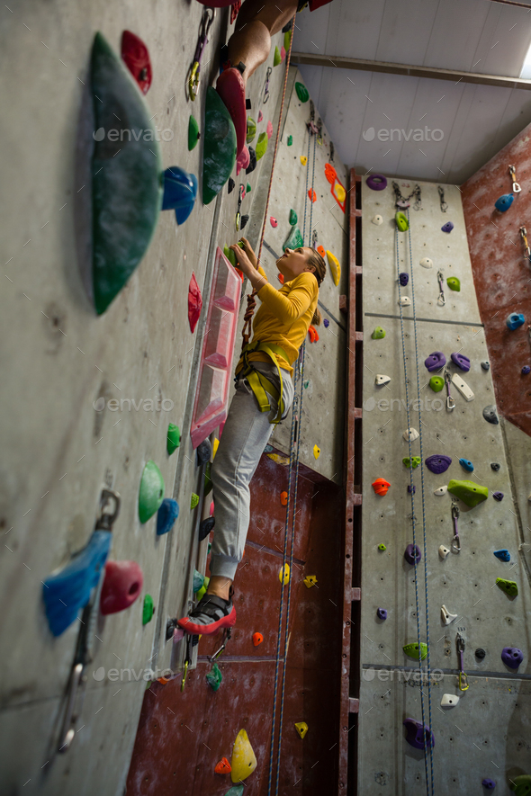 Full length of female athlete rock climbing in club - Stock Photo - Images