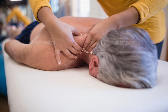Shirtless senior male patient lying on bed receiving neck massage from female therapist - Stock Photo - Images