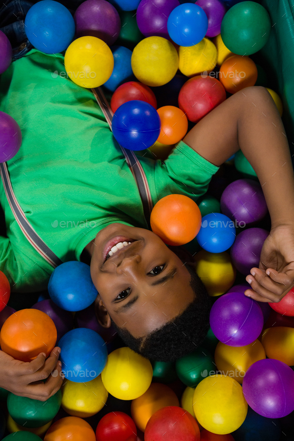 Overhead view of happy boy in ball pool - Stock Photo - Images