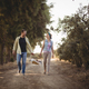 Free Download Cheerful couple carrying basket while walking on dirt road at olive farm Nulled