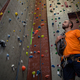 Free Download Low angle view of trainer with rope standing by climbing wall in gym Nulled
