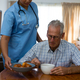 Free Download Doctor serving food to senior man at table in nursing home Nulled